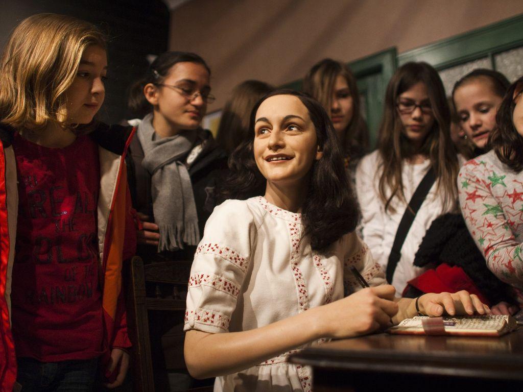 Anne Franks Wachsfigur zwischen den Besuchern