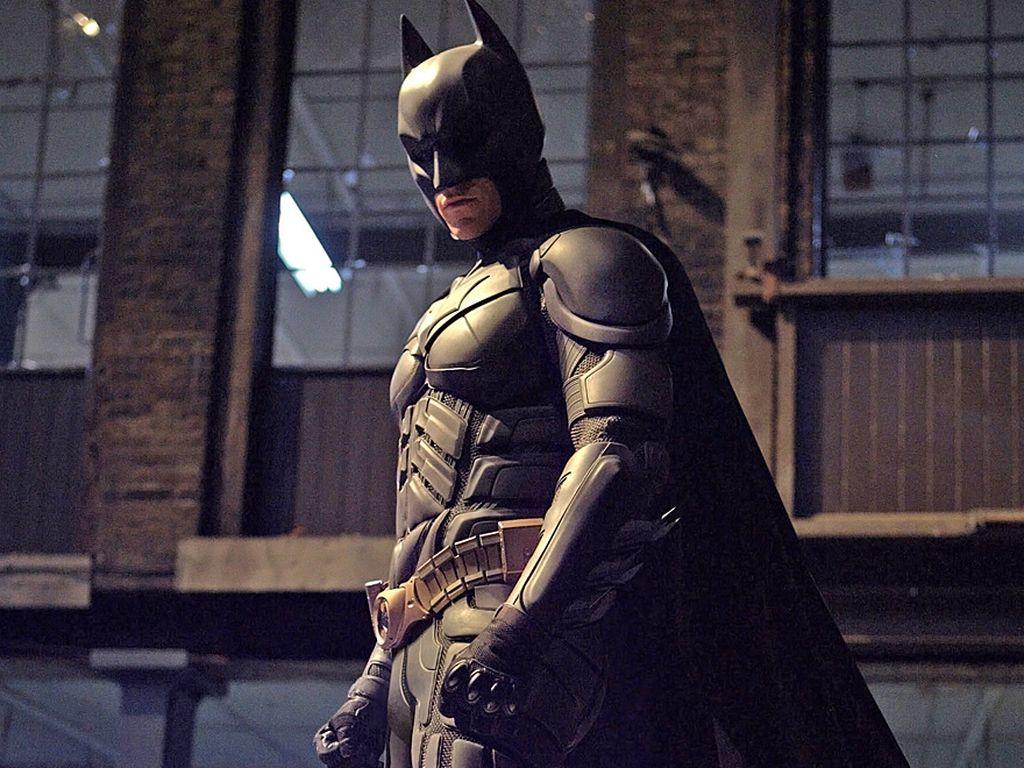 Batman steht auf einem Polizeifahrzeug