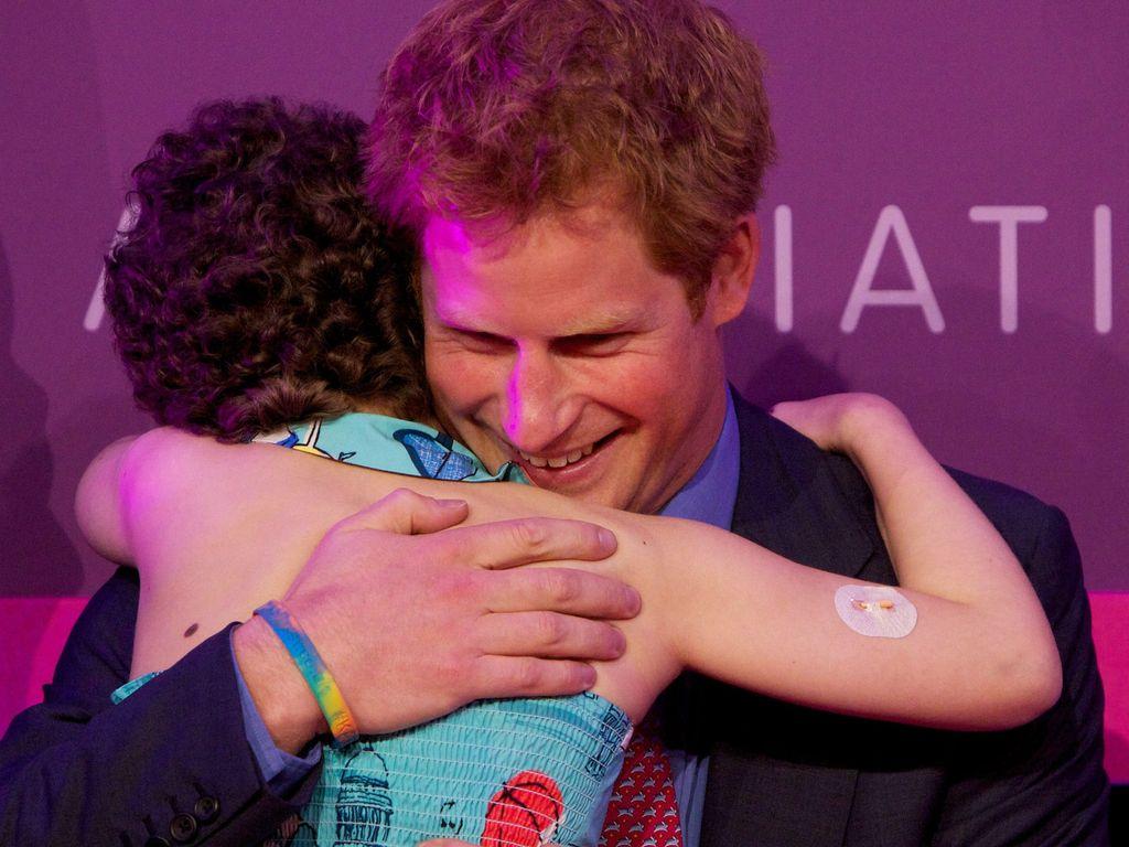 Prinz Harry umarmt ein kleines Mädchen