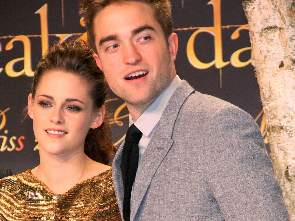 Robert Pattinson in einem grauen Anzug und Kristen Stewart in einem goldenen Kleid