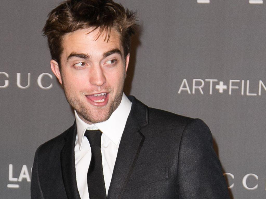 Robert Pattinson lacht und sieht zur Seite