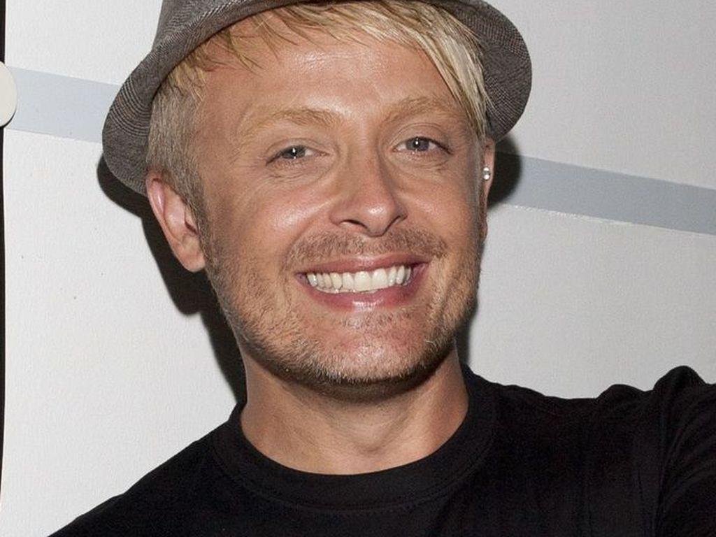 Ross Antony trägt einen Hut und lächelt