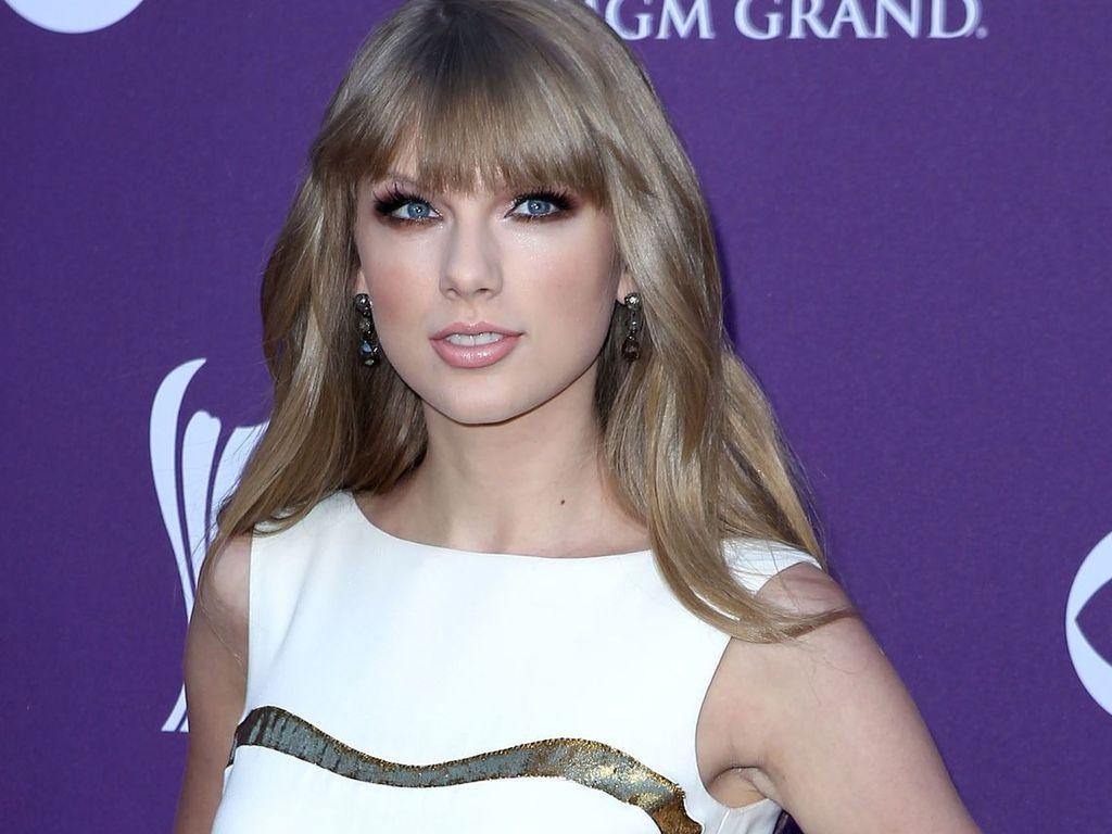 Taylor Swift vor einer lila Fotowand