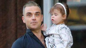 Robbie Williams mit seiner Tochter im Arm