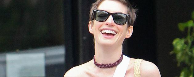 Anne Hathaway lacht mit Arm in Schlinge
