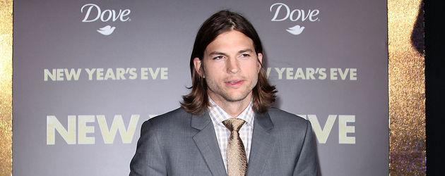 Ashton Kutcher im Anzug mit Händen in den Hosentaschen