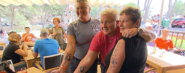 Drei Fans zeigen das Katzenberger-Logo
