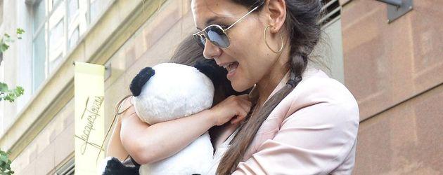 Katie Holmes mit Zopf und Sonnenbrille trägt Suri auf dem Arm