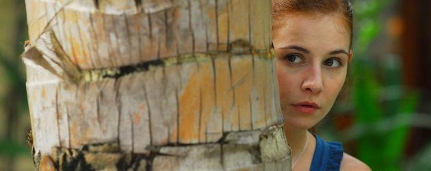 Lena (Josefine Preuß) hinter einer Palme