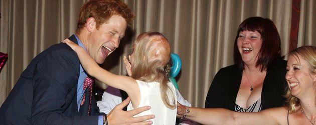 Prinz Harry lacht mit einem kleinen Mädchen