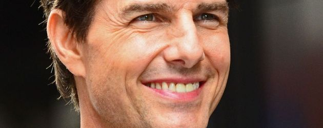 Tom Cruise mit struwweligen Haaren und lächelnd