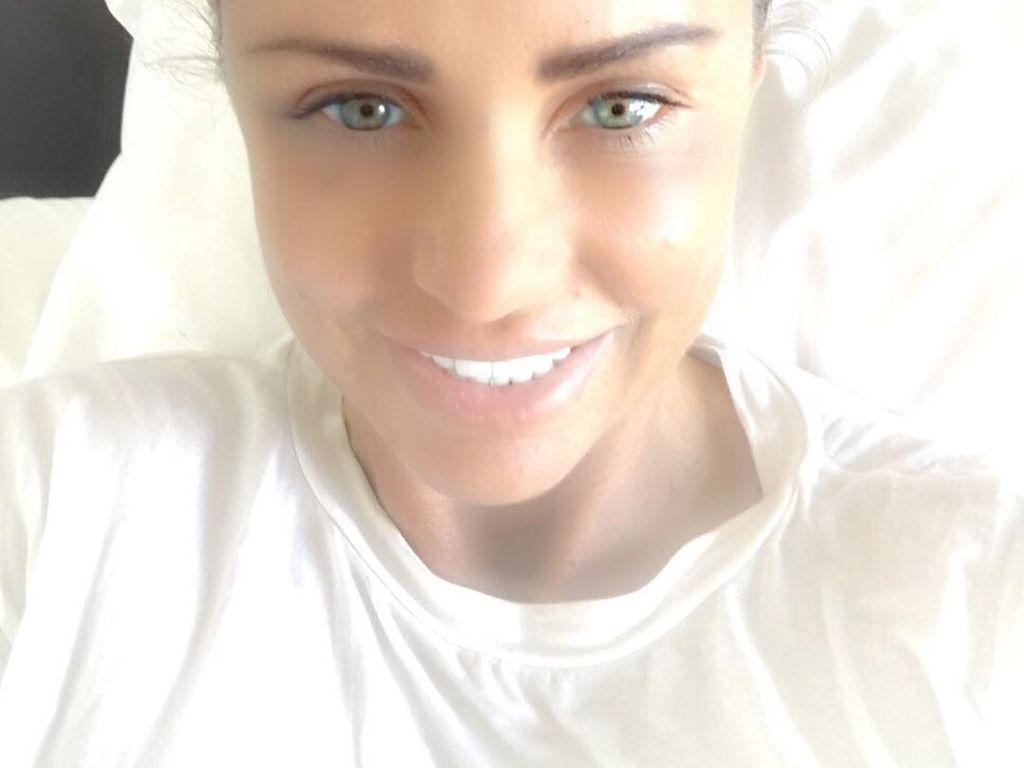 Katie Price freut sich nach einer OP im Krankenhausbett