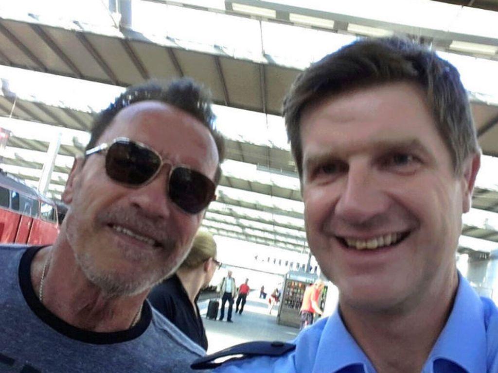 Ein Münchener Polizist macht ein Selife mit Arnold Schwarzenegger