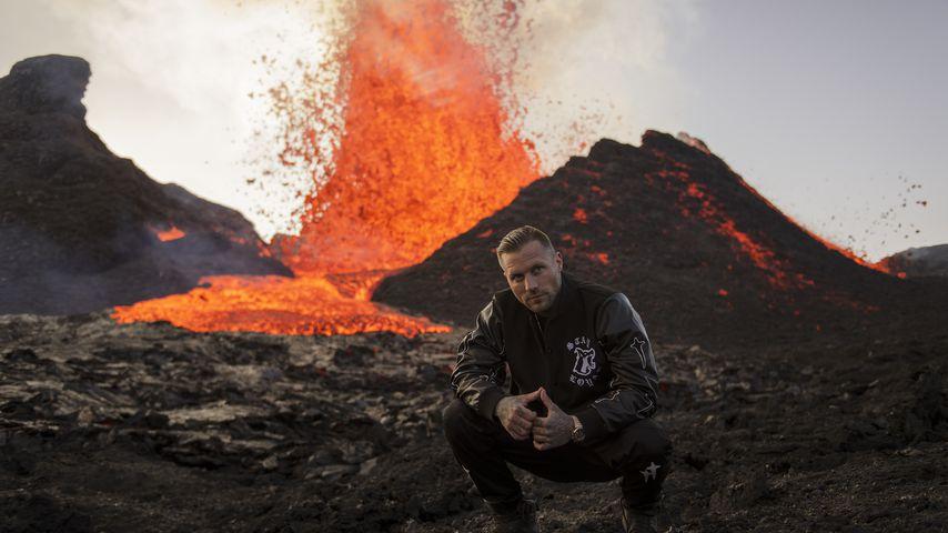Kontra K vor einem ausbrechenden Vulkan