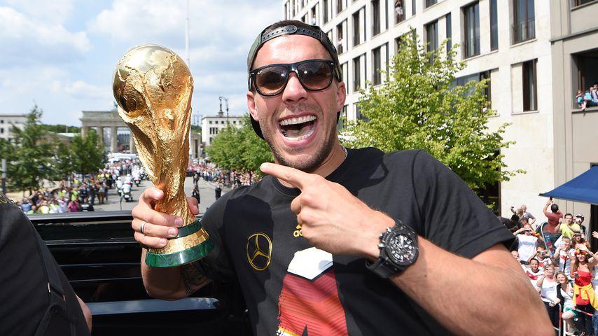 Lukas Podolski mit dem Weltmeister-Pokal in der Hand