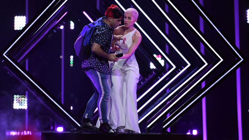 SuRie und ein Flitzer (l.) während ihres Auftritts beim Eurovision Song Contest