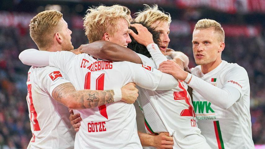 Torjubel rund um Augsburger Felix Götze nach dem 1:1 gegen Bayern München